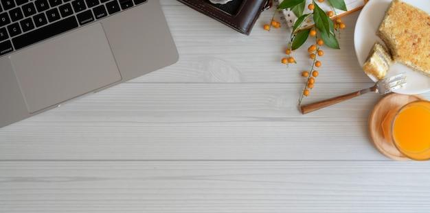 Confortável espaço de trabalho com espaço para cópia e laptop com pão torrado e um copo de suco de laranja