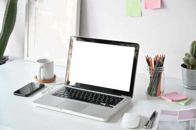 Confortável local de trabalho no escritório com laptop de tela em branco na mesa de madeira branca