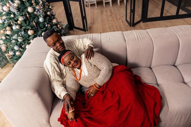 Conforto do lar. casal simpático e positivo descansando no sofá enquanto desfruta de seu tempo em casa