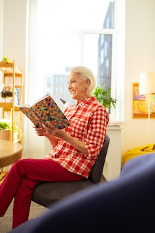 Conforto do lar. mulher alegre e encantada sentada na cadeira lendo um livro interessante