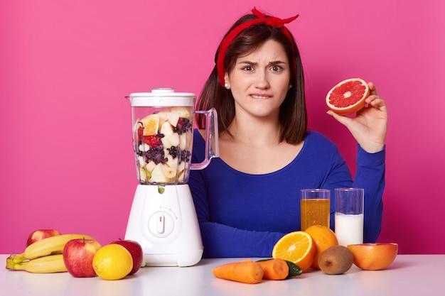 Confusa de cabelo preto emocional fêmea senta-se à mesa, mordendo o lábio, segurando metade de toranja em uma mão, misturando frutas no liquidificador, fazendo doce batido nutritivo para uma refeição saudável na dieta.