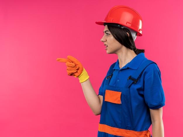 Confusa em pé na vista de perfil, jovem construtora de uniforme usando luvas apontando ao lado