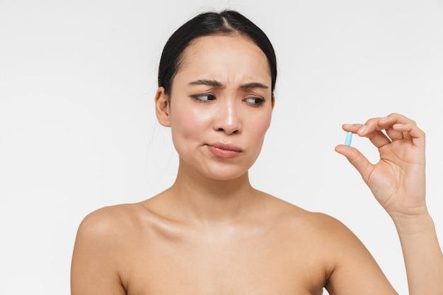 Confusa linda jovem muito asiática com pele saudável posando nua isolada sobre uma parede branca segurando a pílula de vitaminas.