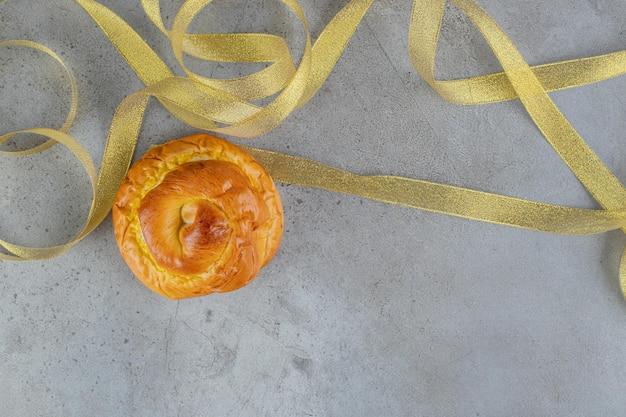 Confusão de fitas amarelas e um único pão na mesa de mármore.