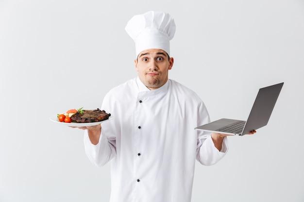Confuso chef cozinheiro usando uniforme em pé sobre uma parede branca, segurando um laptop, mostrando um prato