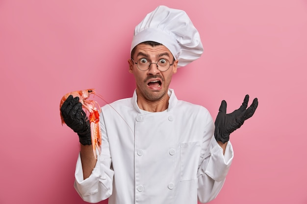 Confuso chef profissional surpreso com produtos de frutos do mar, prepara deliciosos pratos gourmet, exclama negativamente