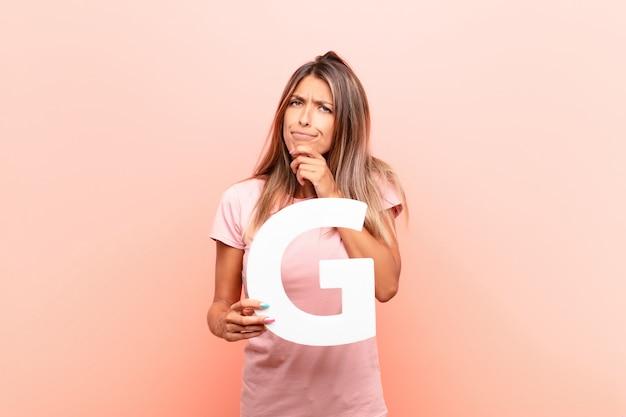Confuso, duvidoso, pensando, segurando a letra g do alfabeto para formar uma palavra ou uma frase.