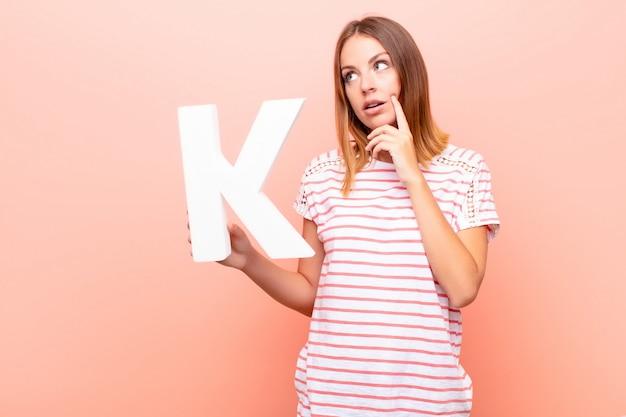 Confuso, duvidoso, pensando, segurando a letra k do alfabeto para formar uma palavra ou frase.