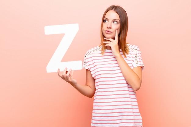 Confuso, duvidoso, pensando, segurando a letra z do alfabeto para formar uma palavra ou frase.
