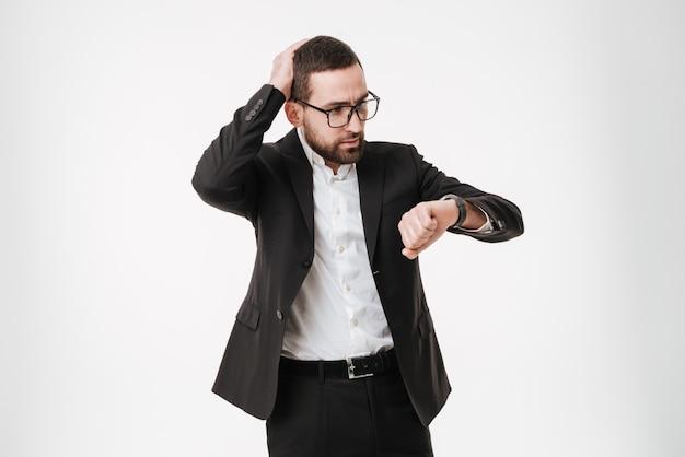 Confuso jovem empresário barbudo olhando para o relógio.
