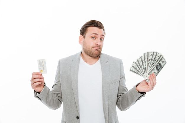 Confuso jovem empresário segurando o cartão de crédito e dinheiro.