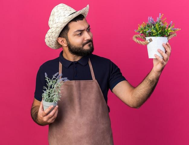 Confuso jovem jardineiro caucasiano com chapéu de jardinagem segurando e olhando vasos de flores isolados na parede rosa com espaço de cópia