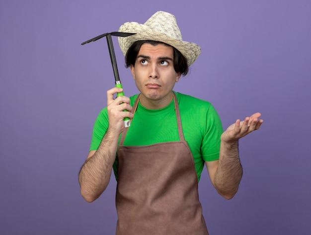 Confuso olhando para o lado, jovem jardineiro de uniforme, usando chapéu de jardinagem, segurando o ancinho enxada