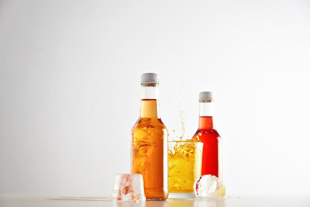 Congelado no ar, respingos de limonada de um cubo de gelo de feltro em um copo com bebida saborosa amarela