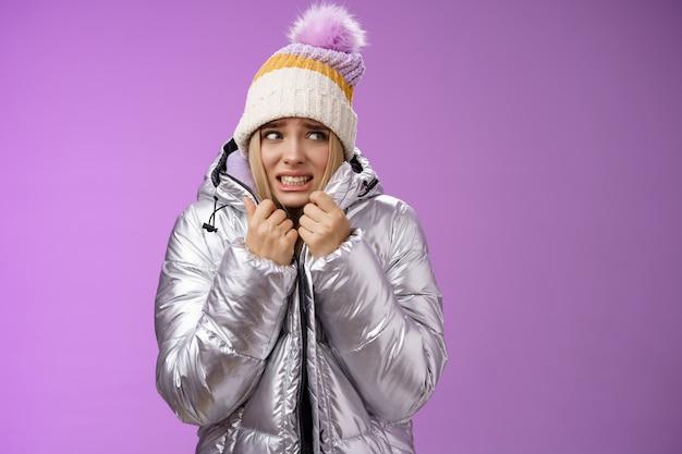 Congelando desconfortável tremendo linda garota loira no chapéu puxar a jaqueta apertada sentindo frio andando montanhas nevadas de baixa temperatura cerrando os dentes curvados tremendo, em pé fundo roxo chateado.