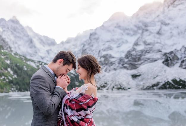 Congelar o casal de noivos está se aquecendo juntos nas montanhas de inverno em frente ao lago congelado