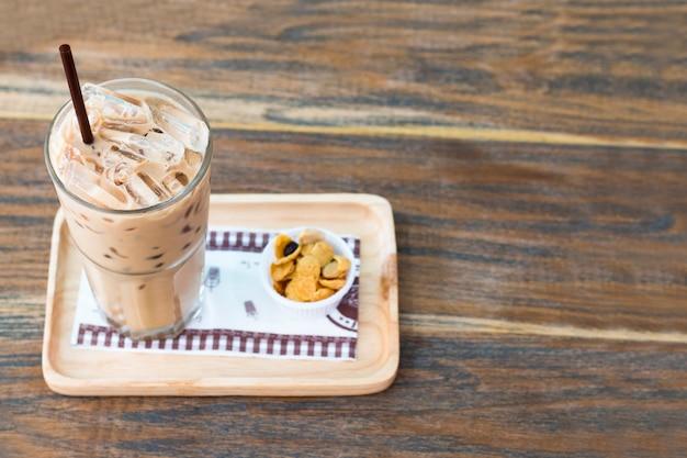 Congele o copo do chocolate e os flocos de milho na madeira. copie o espaço.