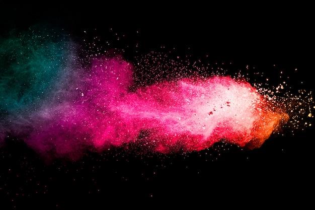 Congele o movimento das explosões de pó coloridas isoladas no fundo preto. partículas de poeira colorida chapinham no fundo.
