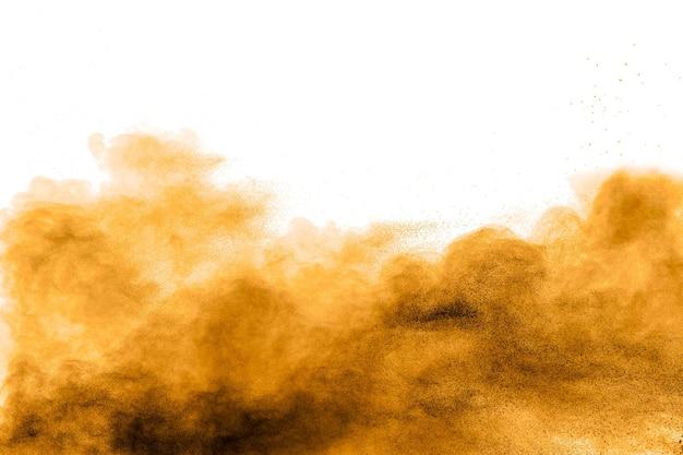 Congele o movimento de explosão de poeira marrom no fundo branco. parando o movimento do pó de holi marrom.