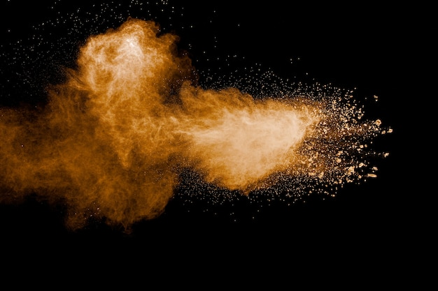 Congele o movimento de explosão de poeira marrom. parando o movimento do pó marrom. pó marrom explosivo sobre fundo preto.