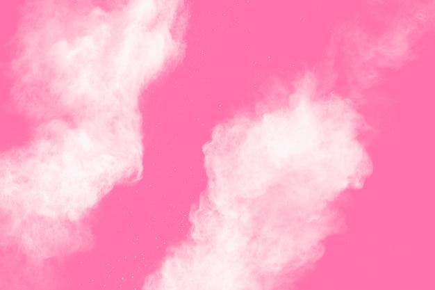 Congele o movimento de um pó branco sobre fundo rosa. explosão de poeira branca abstrata.