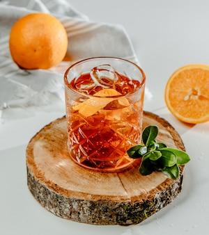 Conhaque com gelo e fatia de laranja