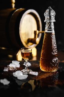 Conhaque e vidro em uma velha mesa rústica de madeira