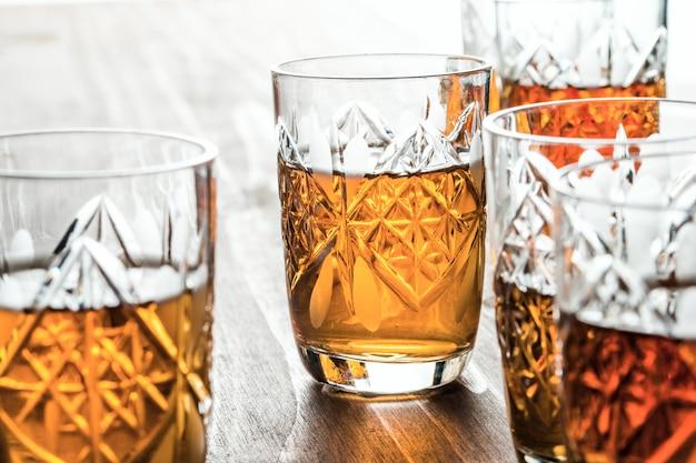 Conhaque em copos de vinho de cristal em uma mesa de madeira
