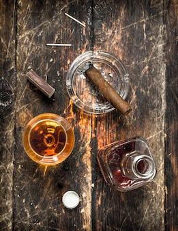 Conhaque francês com charuto. sobre um fundo de madeira.