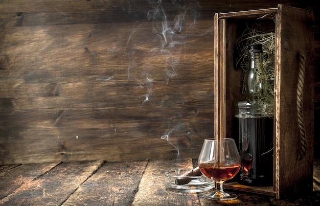 Conhaque francês com um charuto fumegante. sobre um fundo de madeira.