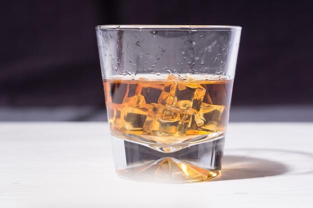 Conhaque velho e saboroso com gelo em um copo cônico de vidro
