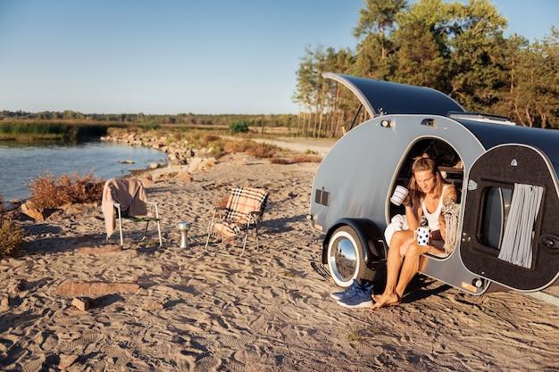 Conheça a manhã. casal apaixonado e fofo, encontrando-se pela manhã em seu trailer compacto, bebendo café