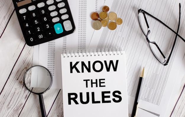 Conheça as regras escritas em um bloco de notas branco perto de uma calculadora, dinheiro, óculos, uma lupa e uma caneta. conceito de negócios