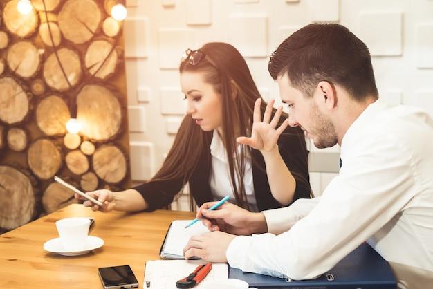 Conhecendo colegas de trabalho, mulher zangada mostra não falar, parar de falar, esperar ou precisa dar uma pausa para o chefe e procurar algo no celular.