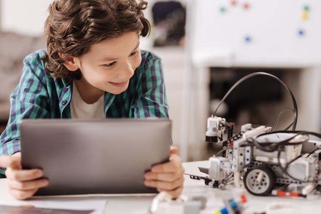 Conhecer um novo amigo eletrônico. menino alegre e extrovertido, sentado na escola e usando um gadget digital enquanto estuda e expressa alegria