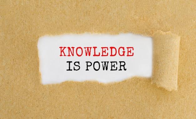 Conhecimento de texto é o poder que aparece por trás do papel marrom rasgado