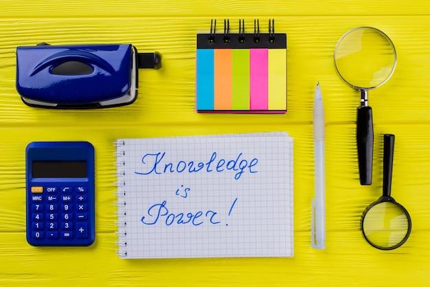 Conhecimento é uma frase de poder escrita no papel do bloco de notas. artigos de papelaria na mesa de madeira amarela.
