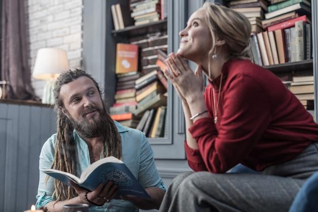 Conhecimento importante. homem barbudo positivo segurando um livro de astrologia enquanto fala com seu cliente