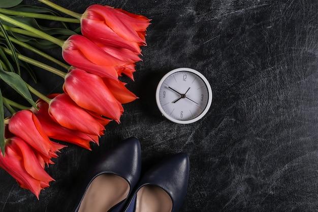 Conhecimento ou dia das mães. tulipas vermelhas com sapatos de salto alto e relógio em um quadro de giz. vista do topo.