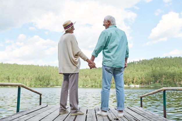 Cônjuges felizes e amorosos em trajes casuais, olhando um para o outro enquanto descansam à beira da água no dia de verão