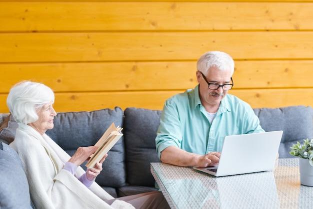 Cônjuges idosos relaxantes sentados no sofá da sala de estar, marido fazendo networking em frente ao laptop e a esposa lendo livro