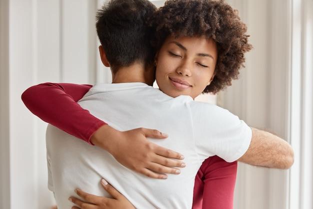 Cônjuges se abraçam afetuosamente no interior de casa
