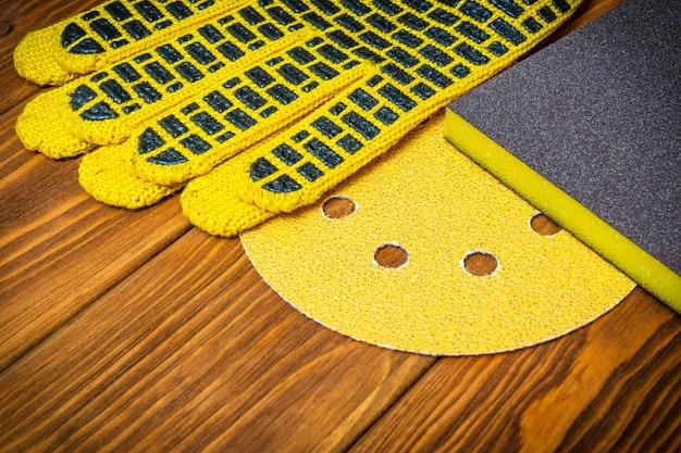 Conjunto amarelo de ferramentas abrasivas e luvas de trabalho no assistente de tábuas de madeira vintage é usado para moer itens