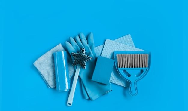 Conjunto azul para limpeza de primavera na casa - trapos, luvas de borracha, esponjas, escova e uma colher com uma vassoura.