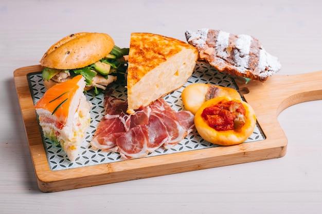 Conjunto café da manhã espanhol para delivery de omelete com batata sanduíche de presunto ibérico em tábua de madeira