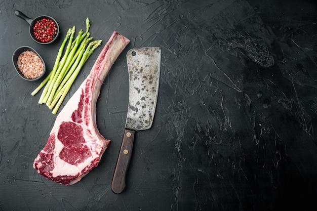 Conjunto clássico de bifes de striploin de carne fresca, corte de tomahawk, na pedra preta