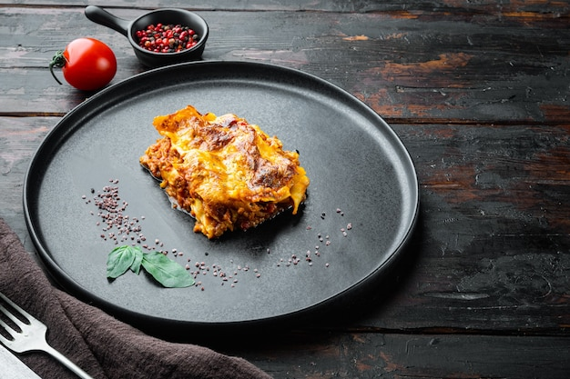 Conjunto clássico de lasanha de carne com queijo bechamel e molho à bolonhesa, no prato, na velha mesa de madeira escura