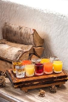 Conjunto colorido de coquetéis alcoólicos em atiradores de copos de shot na mesa de madeira para uma festa alcoólica.