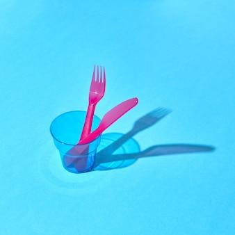 Conjunto colorido de garfo e faca descartáveis em um vidro transparente com longas sombras, lugar para texto.