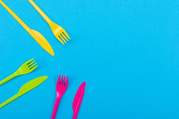 Conjunto colorido de garfos vibrantes e faca isolada no preto